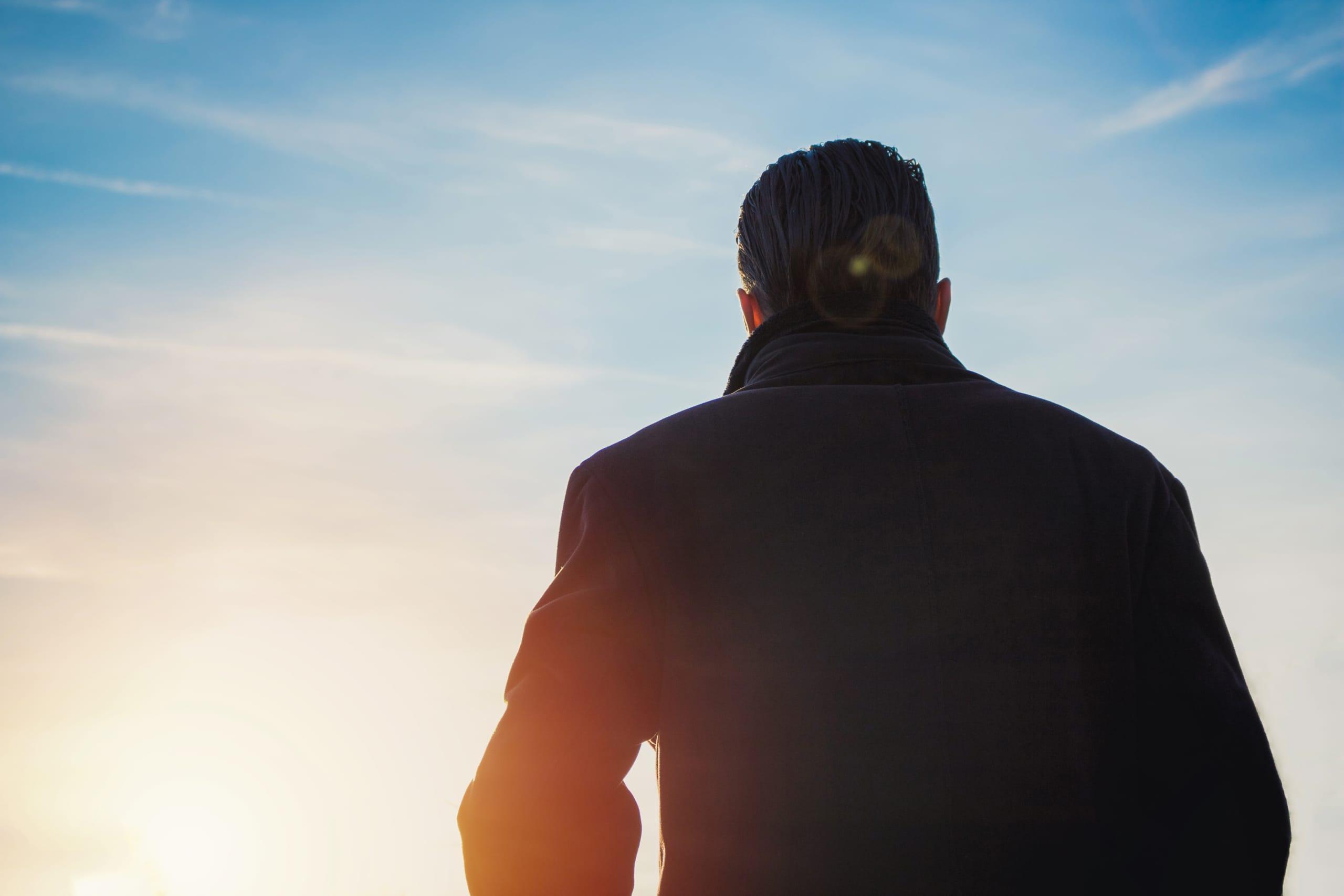 Mann im dunklen Mantel von hinten gegen den blauen Himmel fotografiert