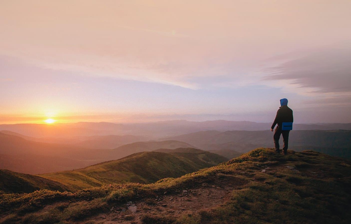 Mann schaut auf einen Sonnenuntergang in den Bergen